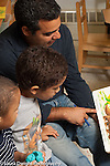 Preschool 3-4 year olds male teacher reading picture book to two boys