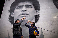 NEW YORK, UNITED STATES - NOVEMBER 25: Fans have a drink by a Mural of Diego Maradona on November 25 2020 in New York. The Argentine soccer legend died at the age of 60, his spokesman announced(Photo by Eduardo Munoz/VIEWpress via Getty Images)