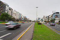 the Avenida 9 Julio Avenue of ninth of July, said to be the world's widest street, lined by trees and modern office block buildings. Publicity posters. Traffic, cars driving past, blurred unsharp due to speed motion Buenos Aires Argentina, South America