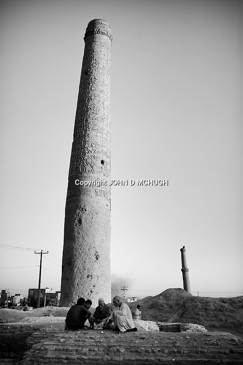 Drug addicts are seen smoking heroin in the shadows of Herat's famous 15th century minarets, 18 September 2013. (John D McHugh)