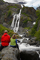 Hikers along waterfall below Cataract Glacier, Harriman Fiord, Prince William Sound, Chugach National Forest, Alaska.