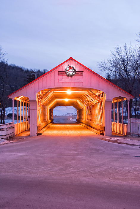 A flashing red traffic light added an interesting tint to this image of the Ashoulet Covered Bridge.