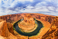 Fisheye view of famous Horseshoe Bend's incised meander on the Colorado River under a cloudy, dramatic sky, near Page city in Arizona, USA