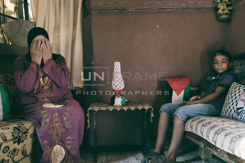 Palestinian Mother and her son. Both were born here in Lebanon and she lives in Shatila camp for 25 years. Their dream of a return is also very present in their house and artcraft they keep to remind themselves. Shatila, Beirut. Lebanon august 2015