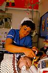 Staff nurse feeding baby child childrens ward Alder Hey Hospital Manchester NHS 1980s 1988 UK