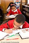 K-8 Parochial School Bronx New York Grade 4 boy writing in class vertical