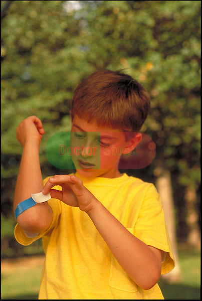 young boy applying a band-aid, bandaging to elbow