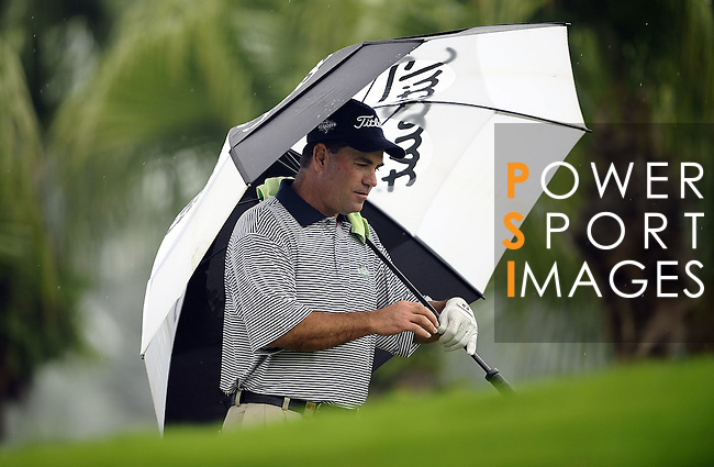 TAIPEI, TAIWAN - NOVEMBER 18:  Tim Thelen of the USA shelters from the rain under an umbrella on the 1st hole during day one of the Fubon Senior Open at Miramar Golf & Country Club on November 18, 2011 in Taipei, Taiwan.  Photo by Victor Fraile / The Power of Sport Images