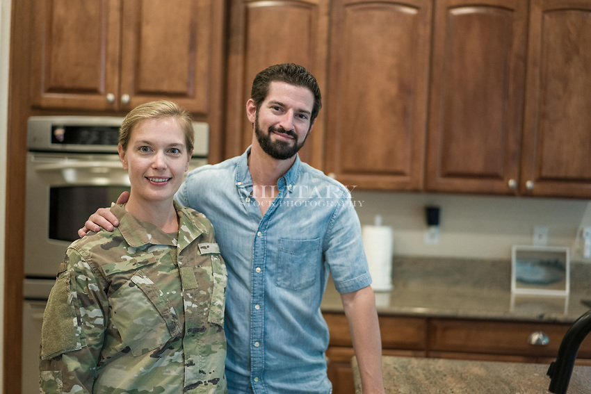 Happy couple at home together. Wife in US military uniform.