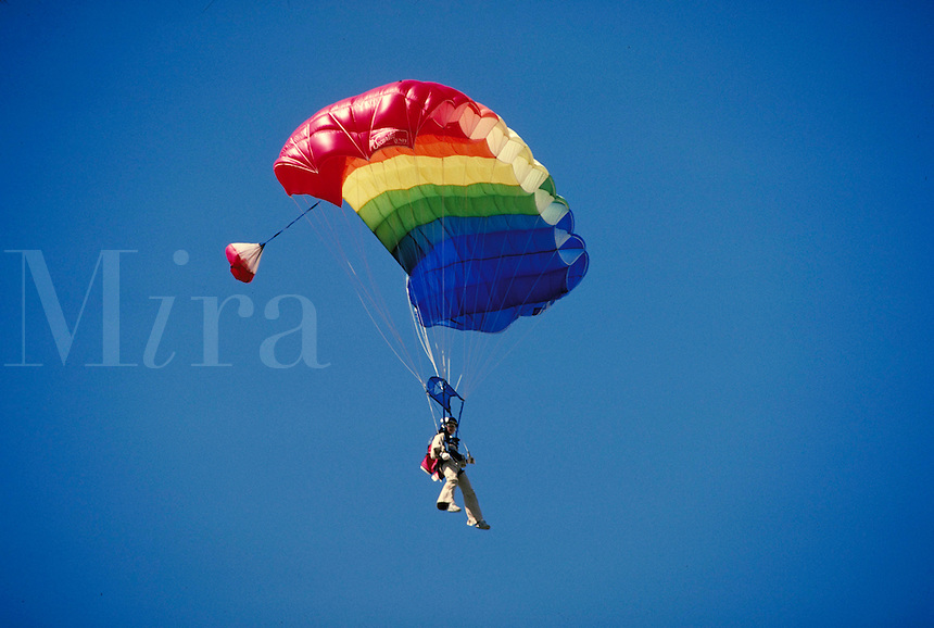 Sky diver guides colorful parachute to landing zone. Connotations - Daring, courage. sports,. Cedar Valley Utah.