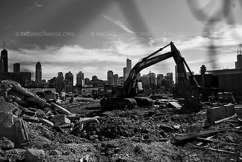 """Chicago , Illinois <br /> USA<br /> May 2008<br /> <br /> Construction cranes takedown one of the last remaining buildings in Chicago's Cabrini green neighborhood. Cabrini-Green is a Chicago Housing Authority (CHA)  public housing development on Chicago's North Side, bordered by Evergreen Avenue on the north, Sedgwick Street on the east, Chicago Avenue on the south, and Halsted Street on the west. At its peak, Cabrini-Green was home to 15,000 people, living in mid- and high-rise apartment buildings. Over the years, gang violence and neglect created terrible conditions for the residents, and the name """"Cabrini-Green"""" became synonymous with the problems associated with public housing in the United States."""