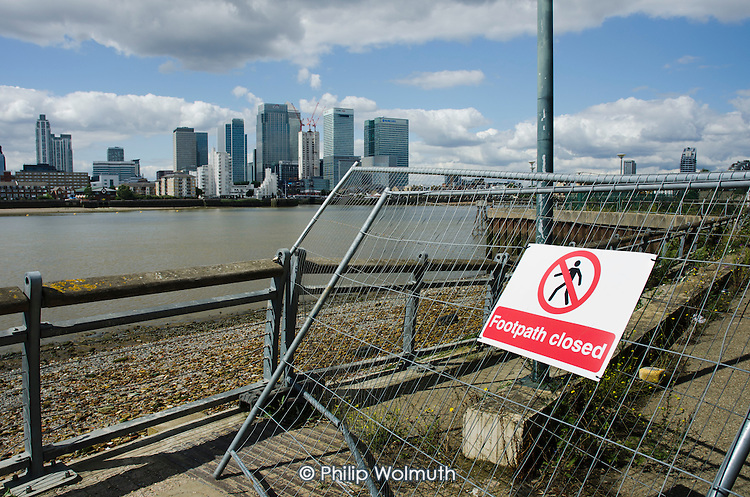 Footpath Closed sign.  Canary Wharf and Barclays, HSBC and Citi bank buildings on the Isle of Dogs, seen from the south bank of the river Thames.