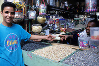Fez, Morocco - Hassan, Vendor of Candy, Nuts, and Seeds, Makes a Sale.  His Customer Wears a Second-hand Shirt Imported from Canada.