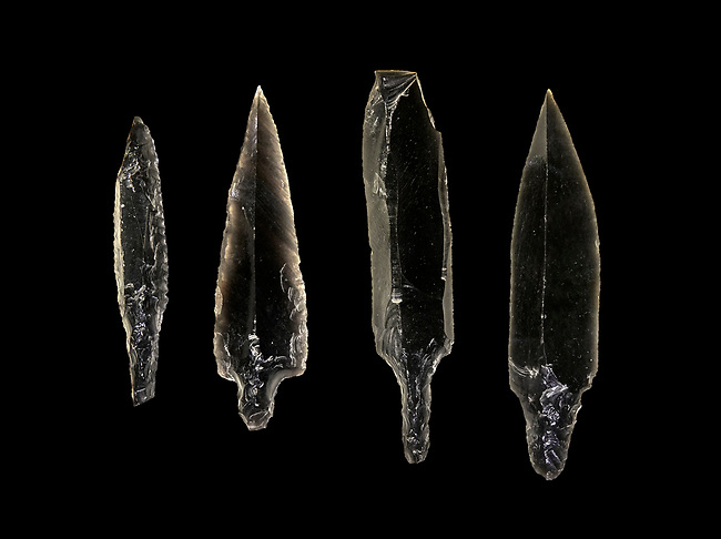 Black obsidian arrow heads. Catalhoyuk Collections. Museum of Anatolian Civilisations, Ankara. Against a black background