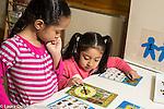 Education preschool 4 year olds two girls playing alphabet animal bingo using spinner and taking turns
