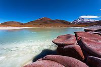 Amazing, red volcanic stones, over the Salar de Aguas Calliente lagoon and 5920m-high, snow-capped Licancabur Volcano, San Pedro de Atacama, Chile