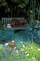 Garden bench in shade, ornamental grasses, flowers, urn 37658