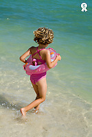Girl (6-7 years) running into water on beach, rear view - Cuba (Licence this image exclusively with Getty: http://www.gettyimages.com/detail/74583311 )