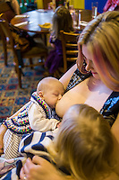 A mother tandem feeds her two children, one about one about twelve weeks old and one about 28 months old, at a sling meet held in the family restaurant and play area in a pub.<br /> Lancashire, England, UK<br /> <br /> Date Taken:<br /> 07-01-2015<br /> <br /> © Paul Carter / wdiip.co.uk