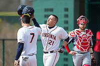 Matt Thaiss (21) of the Virginia Cavaliers knocks helmets with teammate Adam Haseley (7) after hitting a home run against the Hartford Hawks at The Ripken Experience on February 27, 2015 in Myrtle Beach, South Carolina.  The Cavaliers defeated the Hawks 5-1.  (Brian Westerholt/Four Seam Images)
