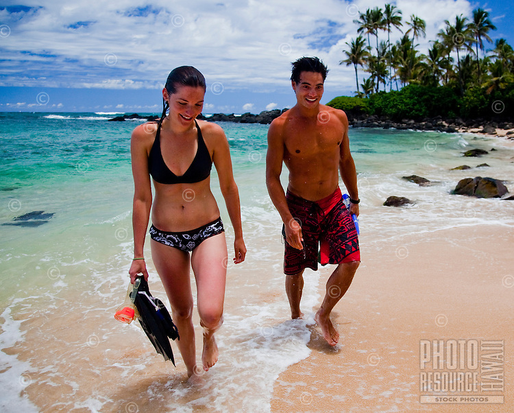 Young couple walking down Laniakea Beach on the North Shore after snorkeling