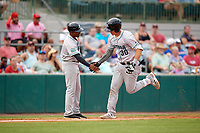 Daytona Tortugas coach Desi Relaford (25) congratulates Tyler Stephenson (30) after hitting a home run in the top of the fifth inning during a game against the Florida Fire Frogs on April 7, 2018 at Osceola County Stadium in Kissimmee, Florida.  Daytona defeated Florida 4-3 in a six inning rain shortened game.  (Mike Janes/Four Seam Images)