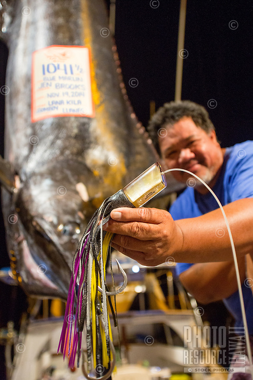 Bomboy Llanes holds up the Bomboy Lure used to catch the 1,041-lb. Pacific blue marlin in the background, Honokohau Harbor, Kailua-Kona, Big Island.