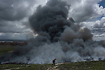 A man walks past a pile of tyres burning in an uncontrolled dump near the town of Sesena, after a fire broke out early on May 13, 2016. A huge waste ground near Madrid where millions of tyres have been dumped was on fire today, releasing a thick black cloud of toxic fumes that officials worry could harm residents nearby.  © Pedro ARMESTRE