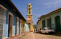 Cobblestone scene with old car in street scene with old church of the old colonial city of Trinidad in Cuba