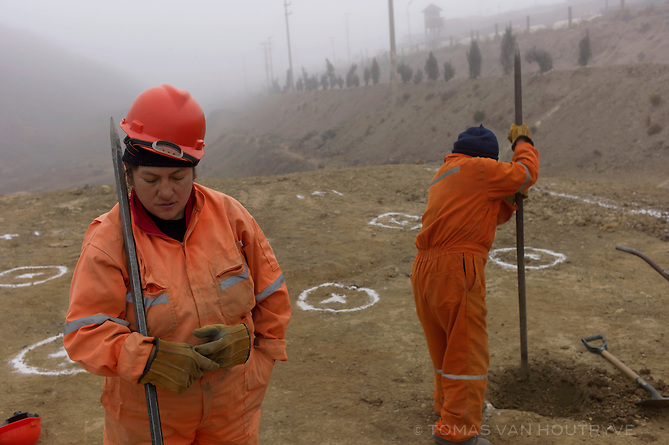 Luz Falcon Toribio, from a team of 10 women, works for Volcan mining company digging holes to plant quinuales trees in the Champamarca neighborhood of Cerro de Pasco on Aug. 15, 2012. The tree planing initiative is a reaction to Peru's Ministry of Environment declaring a 90 day environmental emergency in Champamarca and serveral surrounding areas. Local residents, including some of the women working on the project, commented that the tree planting project was only a symbolic gesture by the mining company and would not resolve the high levels of lead and heavy metal contamination in Champamarca.The open-pit mine run by Volcan is seen bordering the neighborhood of San Juan, viewed from a hill in the Paragsha neighborhood of Cerro de Pasco on Aug. 5, 2012.