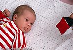 newborn infant girl 1 month old on back closeup hand fisted alert watching dangled high contrast red white and black toy Caucasian horizontal