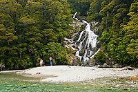 Tourists at Fantail Falls and Haast River near Haast Pass - Mt. Aspiring National Park, New Zealand