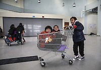 Pictured: Children of migrants amuse themselves in super market trolleys Monday 08 Fabruary 2016<br /> Re: Migrants wait in the Piraeus passenger station to be transported to the migrants' camp in Elliniko, Athens, Greece