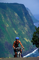 Young athletic woman biking up the steep hill from Waipio Valley on The big Island of Hawaii