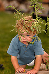 TODDLER HIDING BEHIND THE BRANCHES OF A TOMATO PLANT