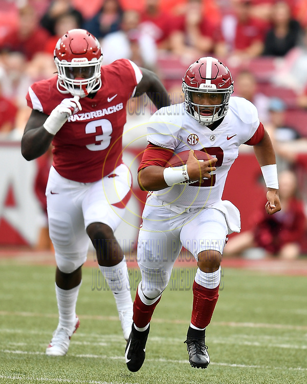 Alabama quarterback JALEN HURTS runs away from Arkansas defensive end MCTELVIN AGIM for a first down during Saturday's game against Arkansas at Donald W. Reynold Razorback Stadium in Fayetteville.