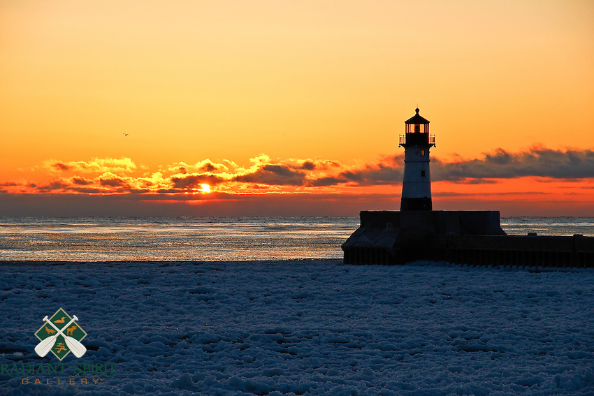 """""""Duluth Winter Sunrise""""<br /> <br /> The icy waters of Lake Superior are painted in pastels by the rising sun. The silhouette of Duluth's lighthouse anchors the serenity of the moment. Ever-changing sky and lake ice conditions make winter sunrises some of the most beautiful and unique. They are well worth braving the cold temperatures."""
