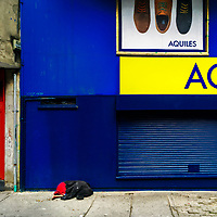 A Colombian handicapped homeless man, covered by a coat, sleeps on the street in the center of Bogotá, Colombia, 26 November 2017.