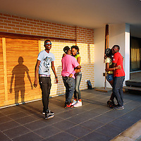 Kuduru/Kuduro music star Cabo Snoop (left) stands next to two couples dancing during the production of a music video for Cabo Snoop's popular hit Windek..