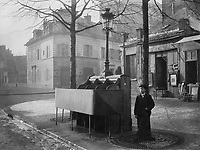 Cast iron and slate urinal with three stalls raised modesty screen, mounted with lamppost and lantern. Boy standing nearby beside lamppost, face blurred by movement. Avenue du Maine, Paris, France.
