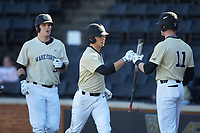 Nick DiPonzio (7) of the Wake Forest Demon Deacons bumps fists with teammate Shane Muntz (11) after scoring a run during the game against the Gardner-Webb Runnin' Bulldogs at David F. Couch Ballpark on February 18, 2018 in  Winston-Salem, North Carolina. The Demon Deacons defeated the Runnin' Bulldogs 8-4 in game one of a double-header.  (Brian Westerholt/Four Seam Images)