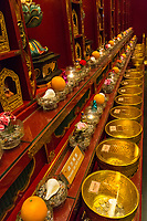 Buddha Tooth Relic Temple, Singapore.  Bowls for Receiving Coin Offerings for the Temple.  Other donations line the wall.