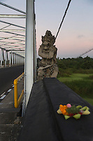 Bali, Indonesia.  Mythical Hindu Figure Guards a Bridge in Southern Bali.  Offering Basket (Canang) in Foreground.