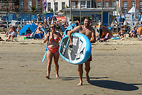 BNPS.co.uk (01202 558833)<br /> Pic: Graham Hunt/BNPS<br /> Date: 7th September 2021.<br /> <br /> Sunbathers flock to the beach to enjoy the scorching hot sunshine at the seaside resort of Weymouth in Dorset.<br /> <br /> Paddle boarders head to the sea with their board across the beach.