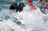 Two 470 sailors have some trouble blasting through a wave during racing