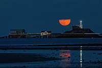 A May super moon, known also as a flower moon is seen rising over Mumbles Lighthouse next to the RNLI boat houses near Swansea, Wales, UK. Wednesday 26 May 2021