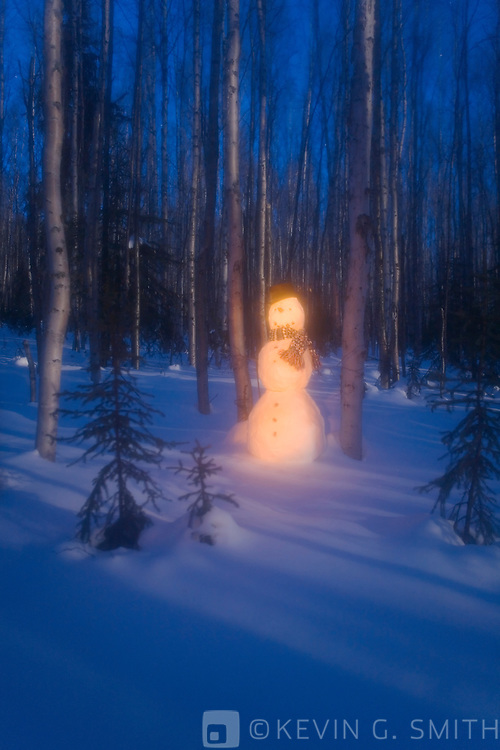 Snowman with top hat standing in a moon lit birch forest. Glowing light, blue color, twilight, Fairbanks Alaska.