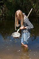 Mädchen, Kind mit selbstgebasteltem Kescher aus Küchensieb, Schlauchschellen, Stock, Drahtkescher, keschern