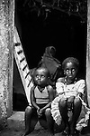 Two cousins sit in the doorframe of a house at night in Djibo in northern Burkina Faso.