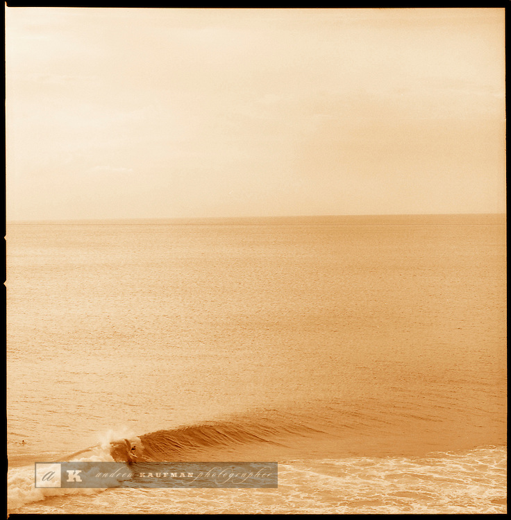 A surfer catches a wave at Padang Padang on Bali's Bukit. The wave is also known as the Bali Pipeline.